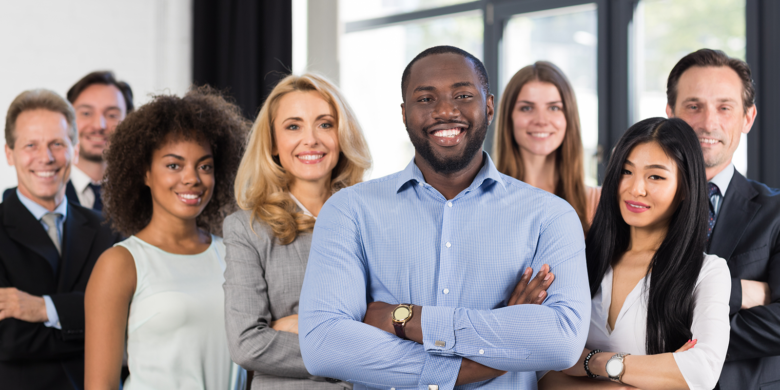 A diverse group of young professionals smiling with arms folded
