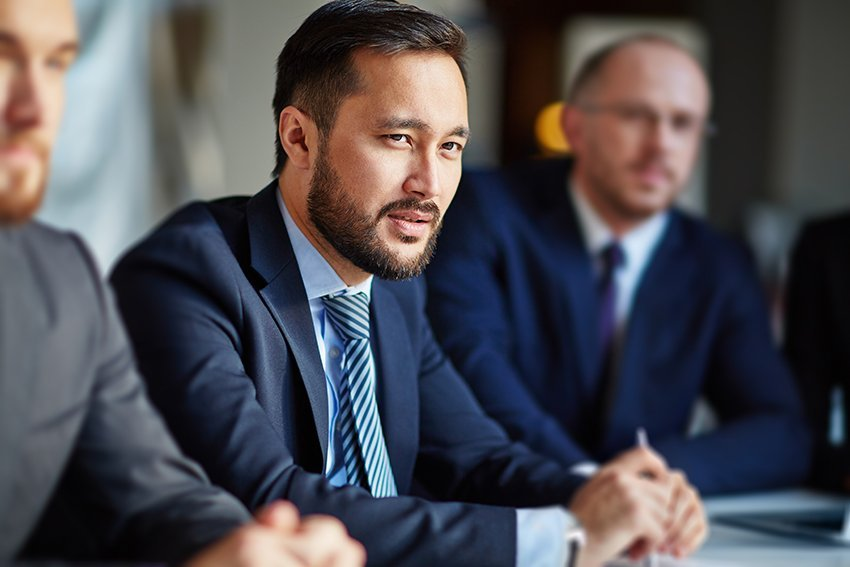 attractive asian man wearing a blue suits listens intently during a business meeting
