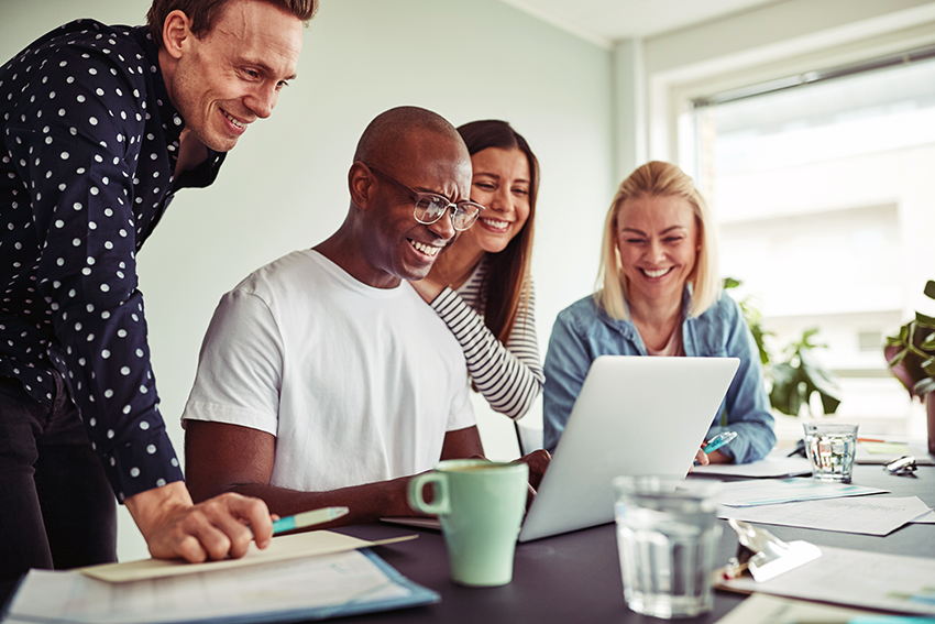 A diverse group of smiling professionals work on their computers in a bright and casual work environment