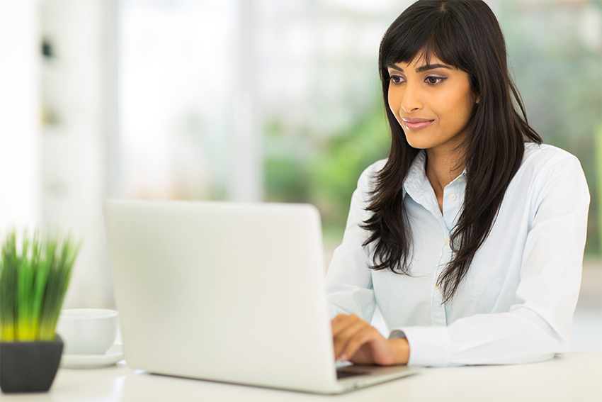 Female remediators types on her computer while at her desk.