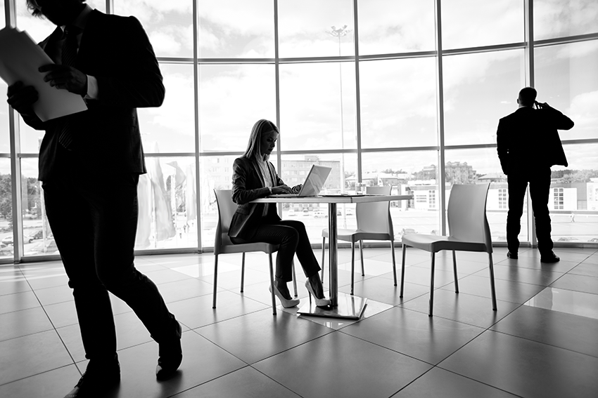 Monochrome view of busy upscale office will floor to ceiling glass windows.