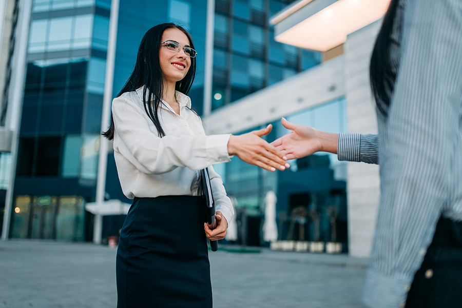 Business woman outside of a skyscraper, shakes hands with a male colleague