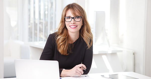 Professional woman with glasses sits in a white office with her laptop open