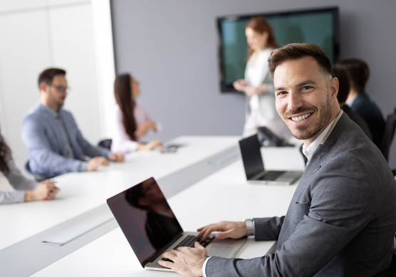 Male business professional smiles as he works on his laptop in a training class